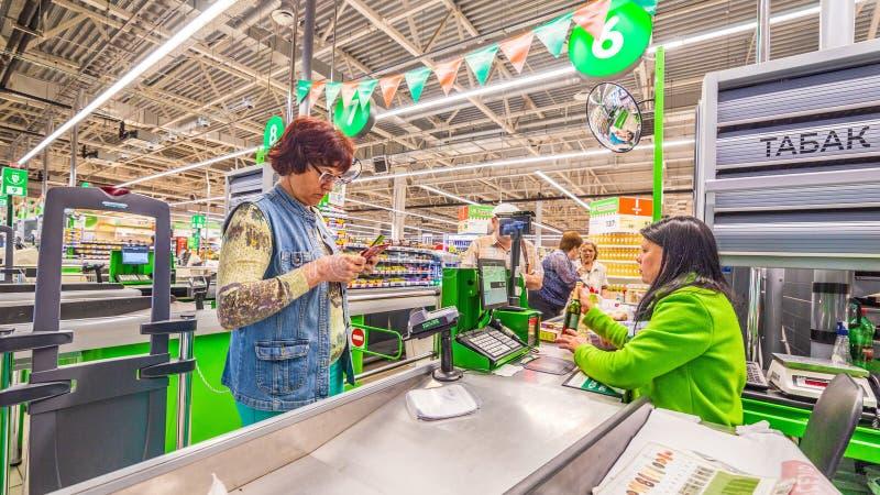 Una bella donna matura sta pagando l'acquisto dei prodotti nel supermercato dalla carta di credito Testo russo: tabacco fotografia stock