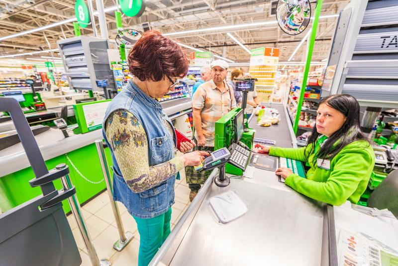 Una bella donna matura sta pagando l'acquisto dei prodotti nel supermercato dalla carta di credito Testo russo: tabacco fotografia stock libera da diritti