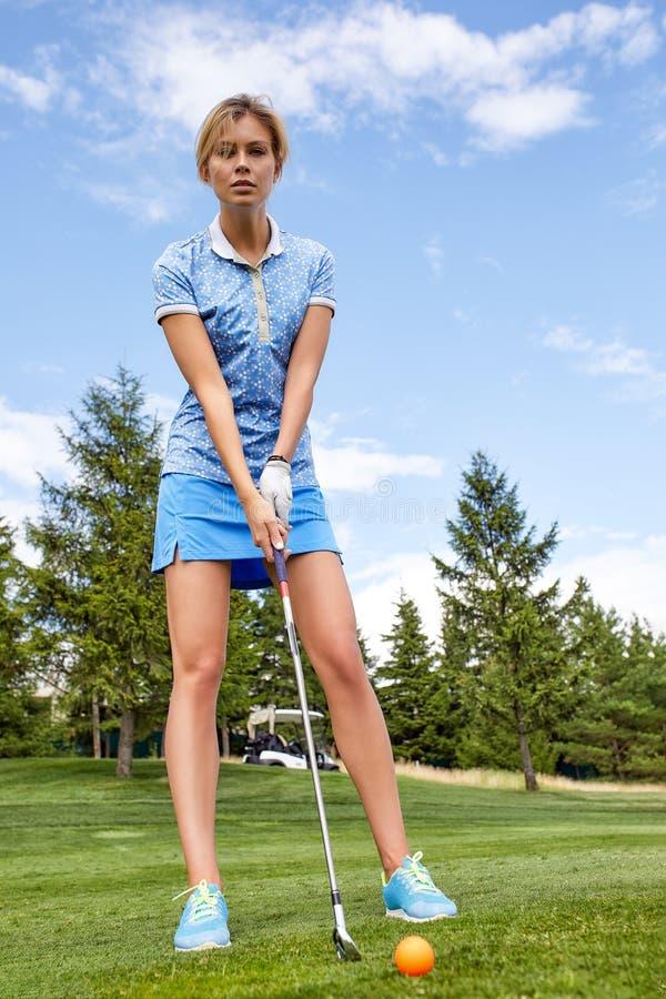 Una bella donna mentre giocava il golf sta preparandosi per colpire la palla davanti al foro su un fondo verde del campo fotografia stock