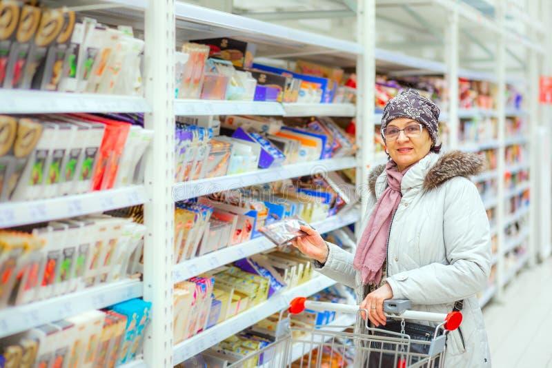 Una bella donna sceglie il cioccolato in un grande deposito fotografia stock libera da diritti