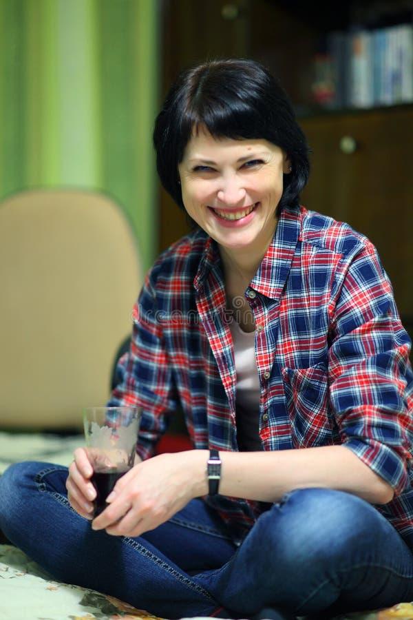 Una bella donna sorridente con un vetro in sua mano attraversa le sue gambe fotografie stock libere da diritti