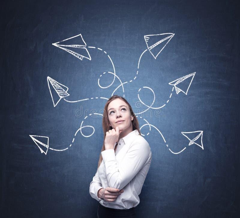Una bella donna sta riflettendo circa le soluzioni possibili del problema complicato Molte frecce con differenti direzioni sono t immagine stock