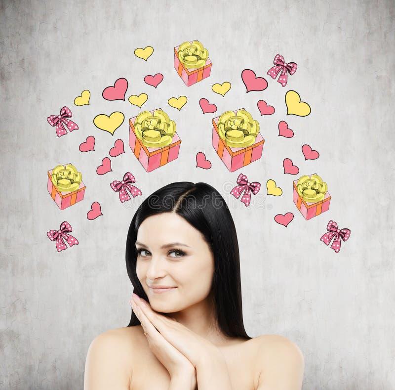 Una bella donna sta sognando del regalo Le icone del cuore e del regalo sono attinte il muro di cemento fotografie stock libere da diritti