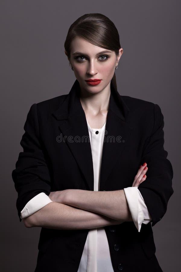 Una bella donna in un rivestimento nero e nei pantaloni neri, con una creatina immagini stock libere da diritti
