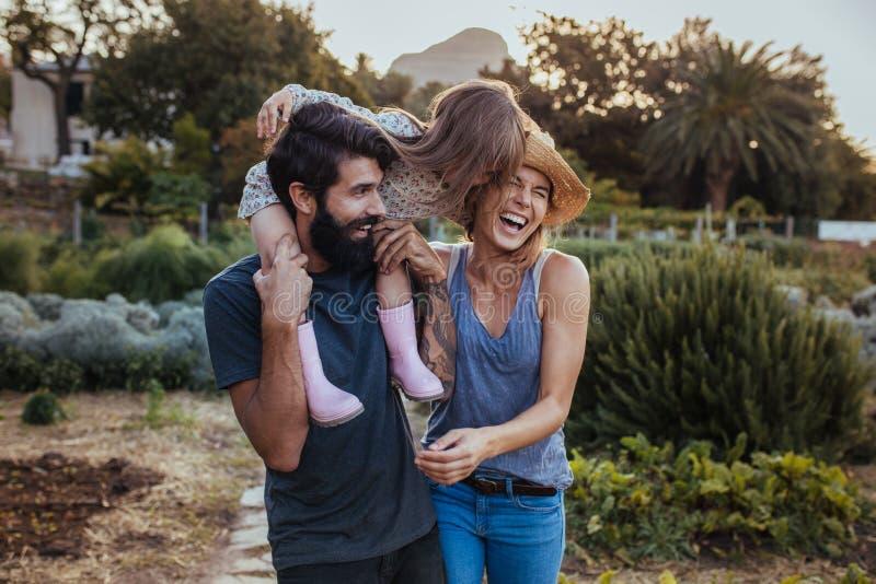 Una bella famiglia di tre divertendosi alla loro azienda agricola fotografia stock