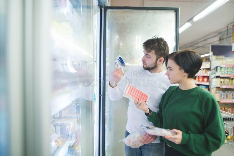 Una bella giovane coppia sceglie gli alimenti congelati vicino al frigorifero in un supermercato immagine stock