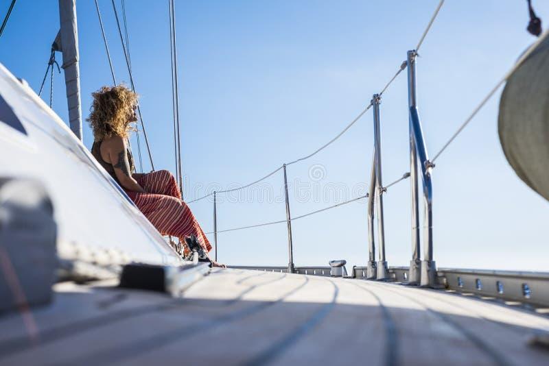 Una bella giovane donna adulta e ricciola seduta sul molo di una barca a vela che si gode il sole durante un viaggio di vacanza e immagini stock