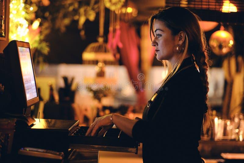 Una bella giovane donna allo scrittorio in un ristorante fotografia stock