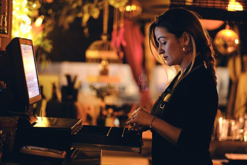 Una bella giovane donna allo scrittorio in un ristorante fotografie stock