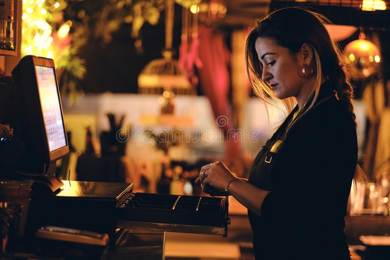 Una bella giovane donna allo scrittorio in un ristorante immagine stock