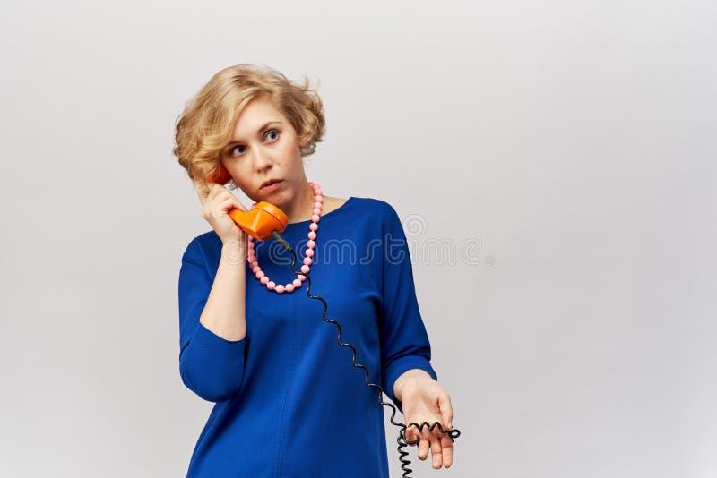 Una bella giovane donna con brevi capelli biondi ondulati in un vestito blu classico tiene un retro microtelefono dal suo telefon fotografia stock