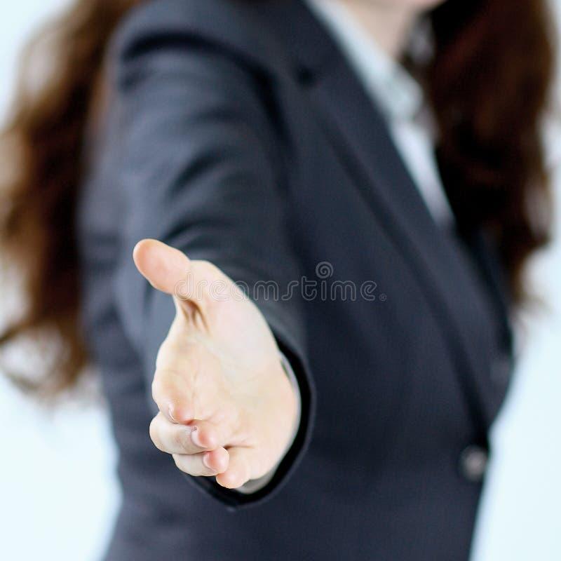 Una bella giovane donna sorridente di affari, soddisfatto e sorridendo, di una mano aperta pronta a sigillare un affare o un benv immagine stock libera da diritti