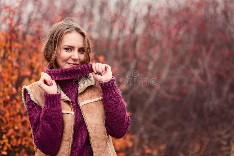 Una bella giovane donna in un maglione caldo in autunno fotografie stock
