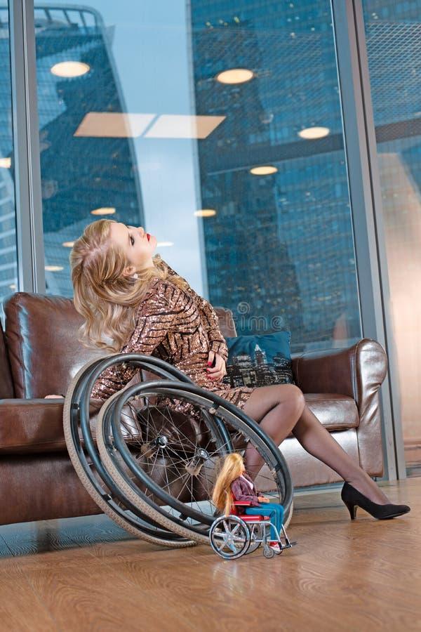 Una bella giovane ragazza bionda in un vestito alla moda con un'inabilità, posante su un sofà di cuoio contro i precedenti immagine stock