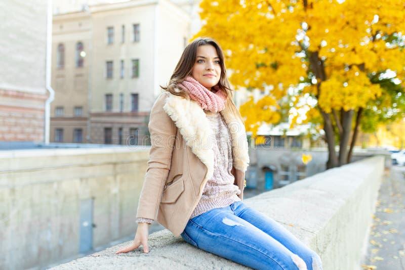 Una bella giovane ragazza castana cammina attraverso la città di autunno nei raggi di luce solare calda immagine stock libera da diritti