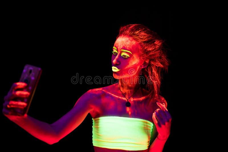 Una bella giovane ragazza sexy con pittura ultravioletta sul suo corpo che balla nello scuro e che fa selfie Donna graziosa con immagini stock