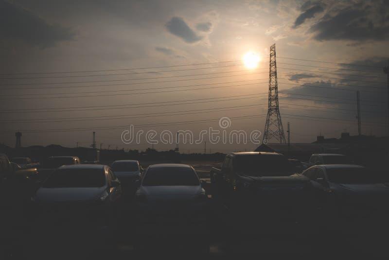 Una bella immagine della siluetta di molti parcheggio in un parcheggio all'aperto, con il contesto del cielo nella sera fotografie stock libere da diritti