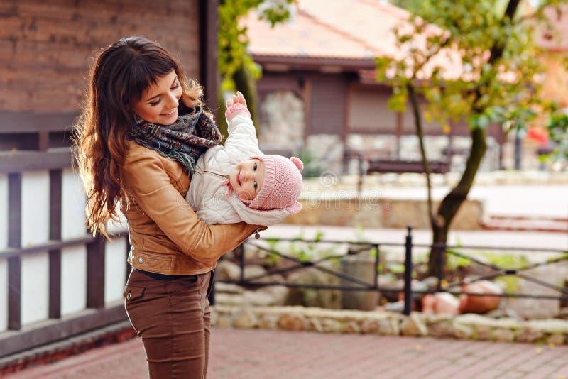 Una bella mamma castana sta tenendo la sua testa giù un bea affascinante fotografie stock libere da diritti
