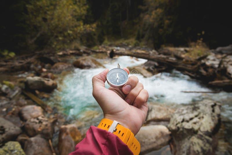 Una bella mano maschio con un cinturino di orologio giallo tiene una bussola magnetica in una foresta conifera di autunno contro  immagini stock libere da diritti