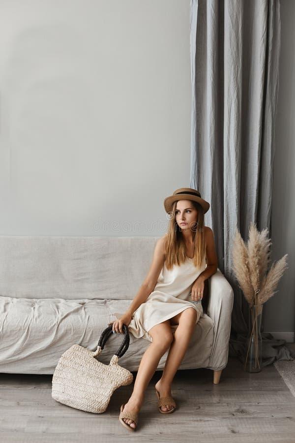 Una bella modelo con un vestido de verano y un sombrero sentados en el sofá en el interior de una casa acogedora Equipo de verano fotos de archivo libres de regalías