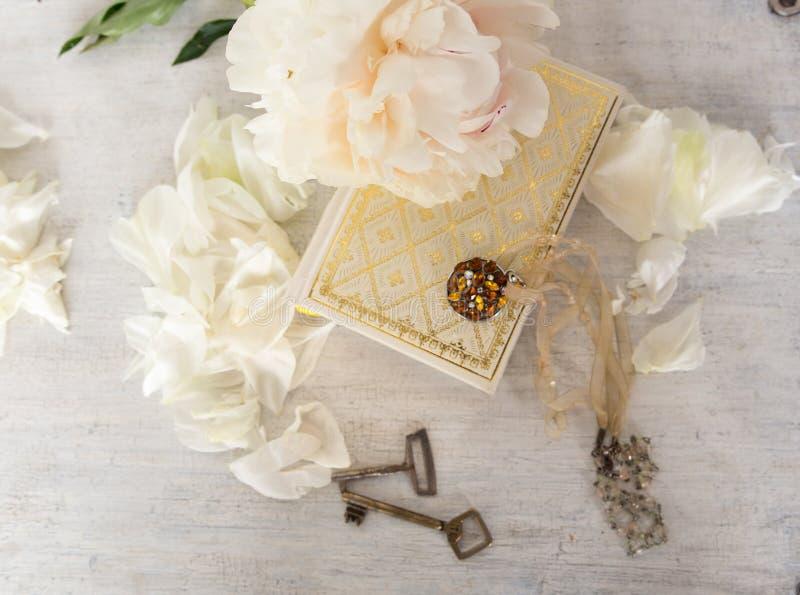 Una bella peonia bianca si trova su un libro con le pagine dorate Vicino sono i petali delicati, le chiavi d'annata e l'abbellime immagini stock
