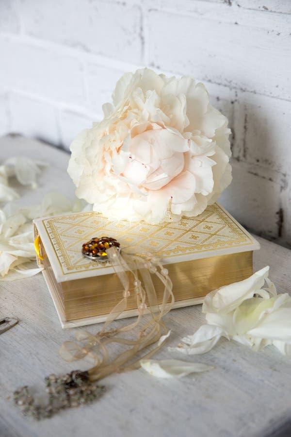 Una bella peonia bianca si trova su un libro con le pagine dorate Vicino sono i petali delicati, le chiavi d'annata e l'abbellime fotografie stock libere da diritti