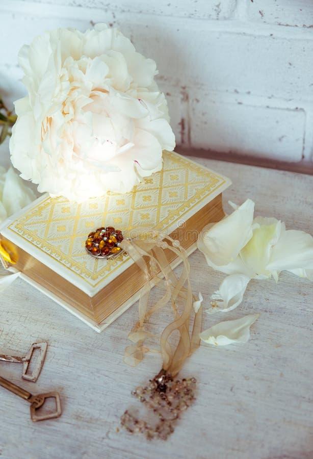 Una bella peonia bianca si trova su un libro con le pagine dorate Vicino sono i petali delicati, le chiavi d'annata e l'abbellime fotografia stock libera da diritti