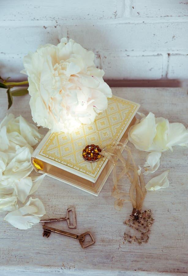Una bella peonia bianca si trova su un libro con le pagine dorate Vicino sono i petali delicati, le chiavi d'annata e l'abbellime immagine stock