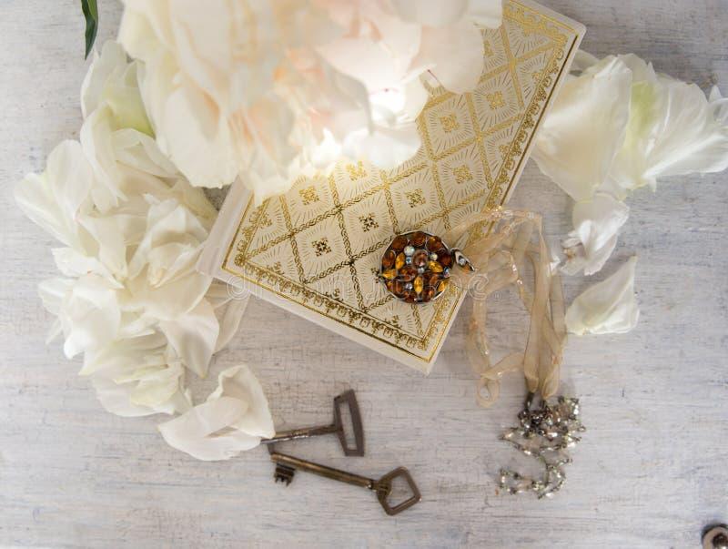 Una bella peonia bianca si trova su un libro con le pagine dorate Vicino sono i petali delicati, le chiavi d'annata e l'abbellime fotografia stock