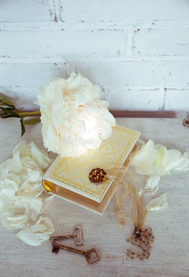 Una bella peonia bianca si trova su un libro con le pagine dorate Vicino sono i petali delicati, le chiavi d'annata e l'abbellime immagine stock libera da diritti