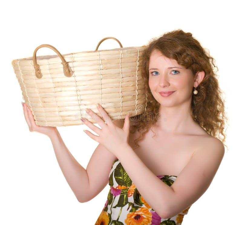Una bella ragazza è un cestino della paglia sulla sua spalla fotografie stock