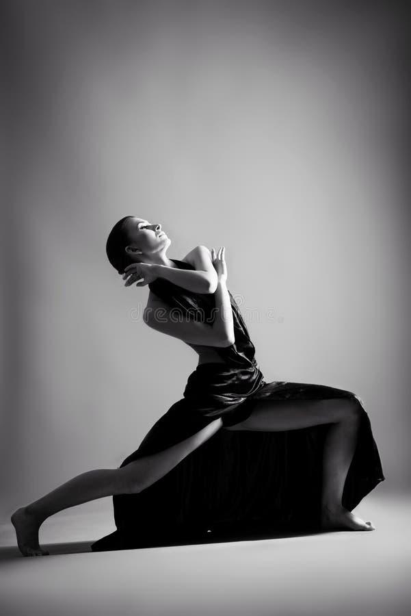Una bella ragazza atletica in un vestito nero sta ballando fotografie stock libere da diritti