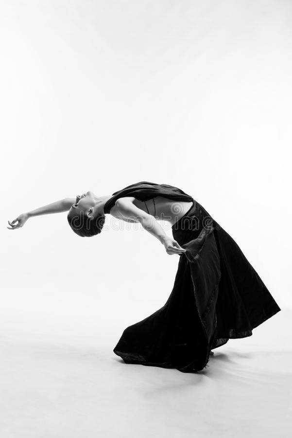 Una bella ragazza atletica in un vestito nero sta ballando fotografia stock libera da diritti