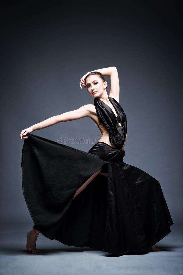 Una bella ragazza atletica in un vestito nero sta ballando immagini stock libere da diritti