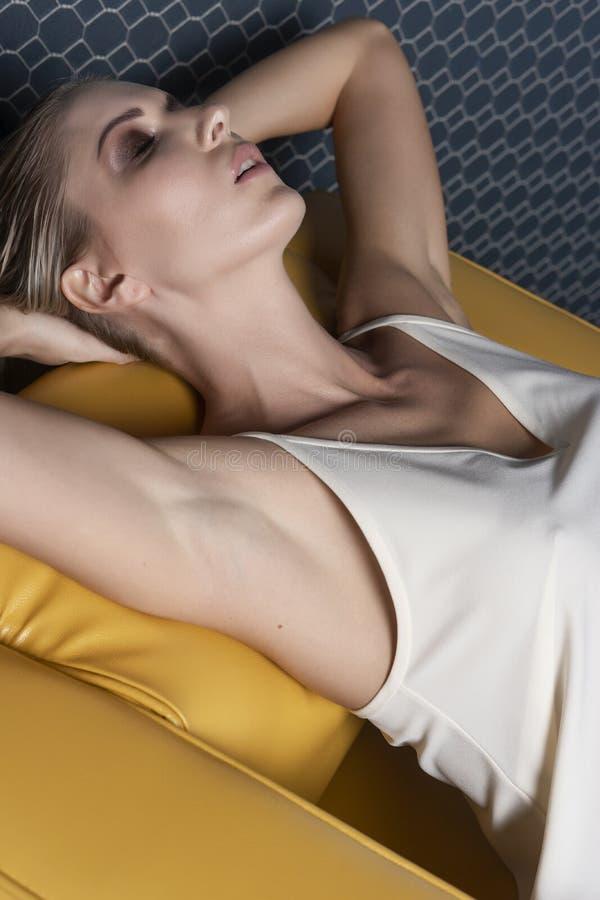 Una bella ragazza bionda che porta un vestito bianco leggero si rilassa su una sedia di cuoio gialla Progettazione di pubblicità, immagine stock libera da diritti