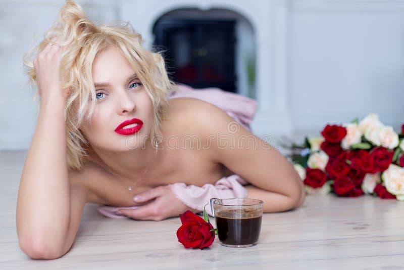 Una bella ragazza bionda giace sul pavimento con una tazza di caffè del mattino caldo e un mazzo di rose immagini stock libere da diritti