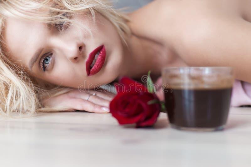 Una bella ragazza bionda giace sul pavimento con una tazza di caffè del mattino caldo e un mazzo di rose fotografia stock