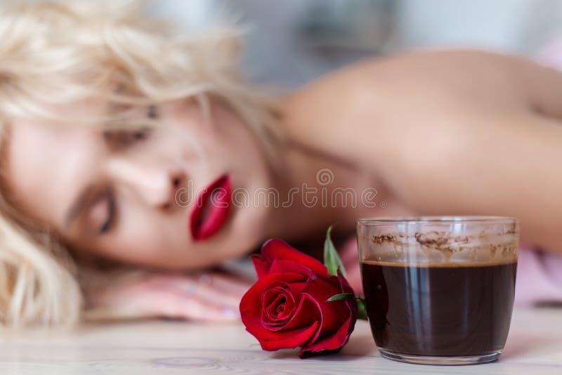 Una bella ragazza bionda giace sul pavimento con una tazza di caffè del mattino caldo e un mazzo di rose immagine stock libera da diritti