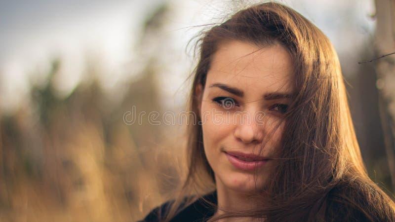 Una bella ragazza castana che posa in un campo sull'autunno Foto di arte fotografia stock libera da diritti