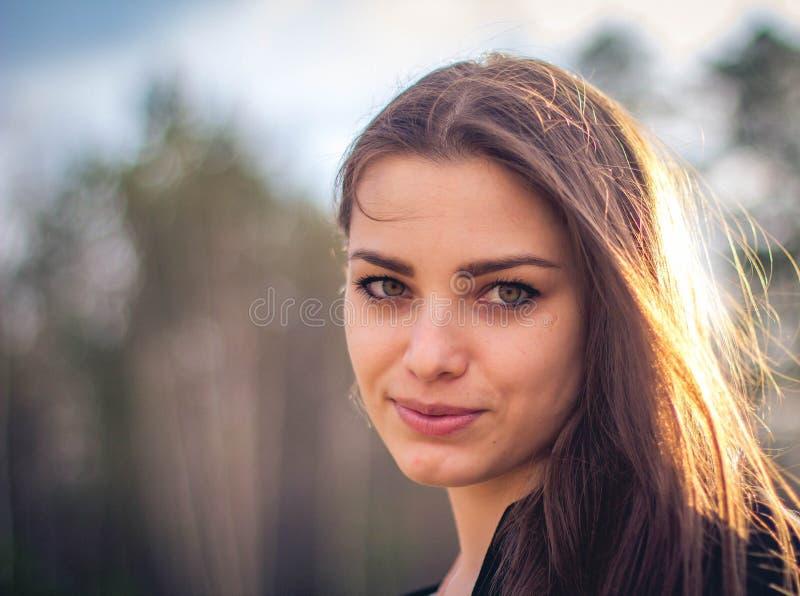 Una bella ragazza castana che posa in un campo sull'autunno Foto di arte fotografia stock