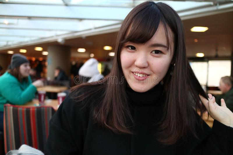Una bella ragazza che gioca con i suoi capelli e che sorride alla macchina fotografica fotografia stock