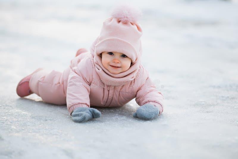 Una bella ragazza che porta una tuta rosa, trovantesi sulla neve in un parco nevoso di inverno immagini stock libere da diritti