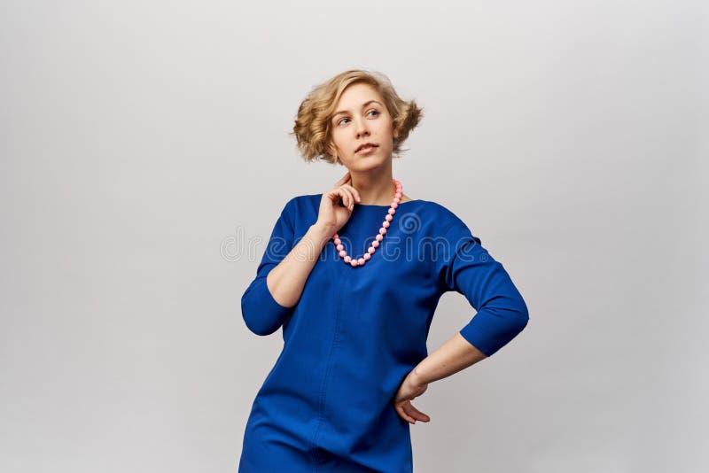 Una bella ragazza con brevi capelli biondi cerca meditatamente e prova a ricordarsi Vestito e perle blu eleganti immagine stock