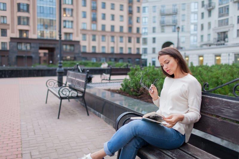 Una bella ragazza con capelli marroni lunghi che si siedono su un banco con un libro, tenente gli occhiali Ha lasciato la casa su immagini stock