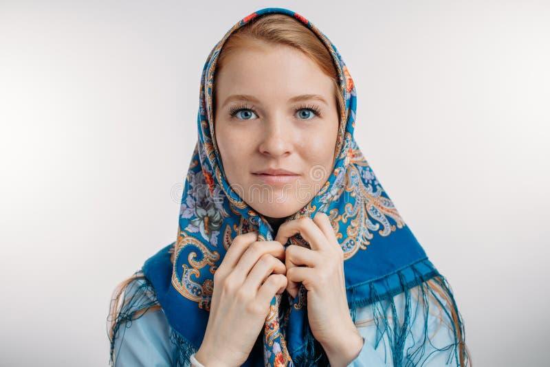 Una bella ragazza con i capelli dello zenzero sta portando lo scialle capo del blu fotografia stock
