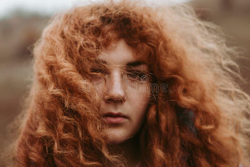 Una bella ragazza con i viaggi rossi dei capelli nei campi ed in prati spaziosi, beve il tè del termos ed ammira il paesaggio immagine stock libera da diritti