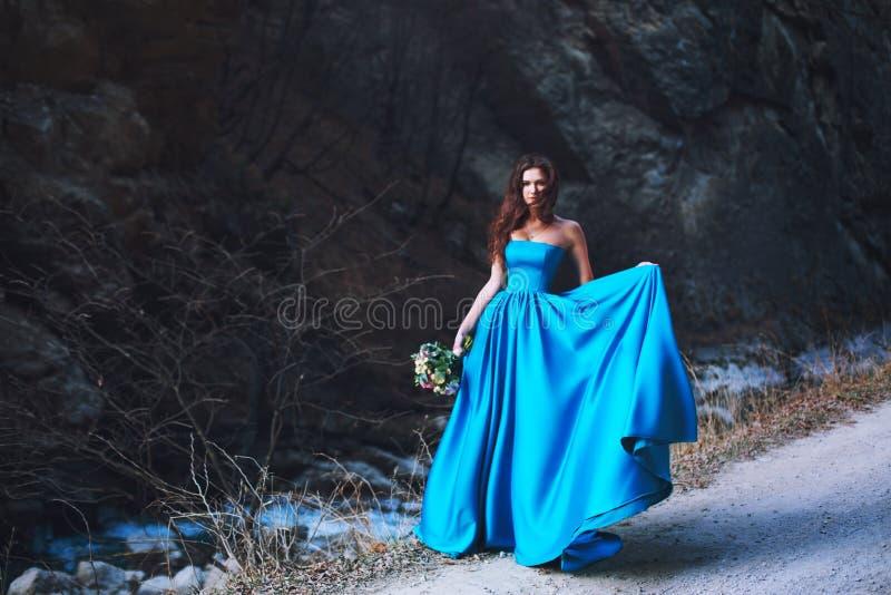 Una bella ragazza con un mazzo di nozze ed in un vestito blu sta stando al piede della montagna fotografia stock libera da diritti