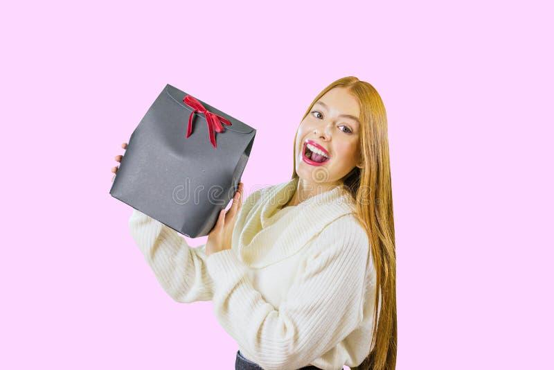 Una bella ragazza dai capelli rossi sveglia che tiene un contenitore di regalo tiene una scatola nera con un nastro di velluto ro immagine stock