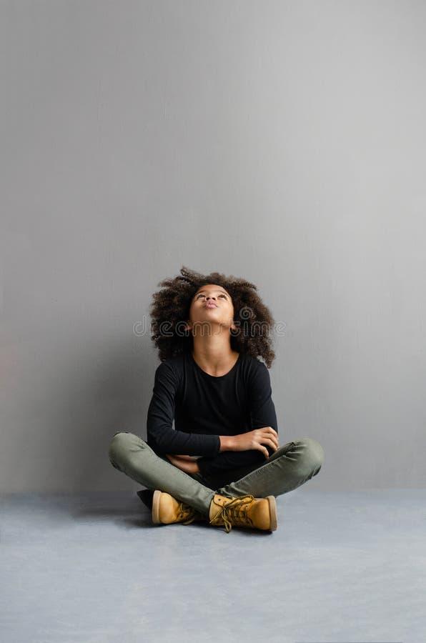 Una bella ragazza dalla carnagione scura si siede meditatamente sul pavimento fotografia stock