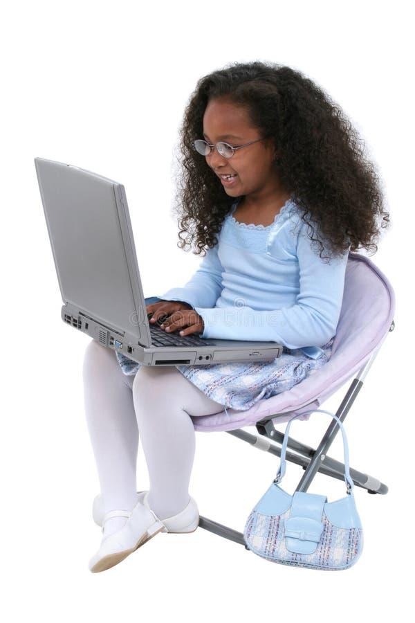 Una bella ragazza di sei anni con il computer portatile sopra bianco immagine stock libera da diritti